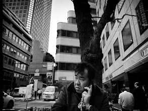 Photo: In the concrete jungle  It's interesting how things look different when viewed through a camera lens. I walk past here every weekday (and sometimes weekend) and generally think of the area below as a pretty open space (for Japan). After taking this shot though, I feel like the buildings are looming, closing in upon everyone.  I like that the guy on the phone has an appropriately worried look! (maybe that's why his keitai/cellphone strap is so massive, full of good-luck charms?)  #creative366project