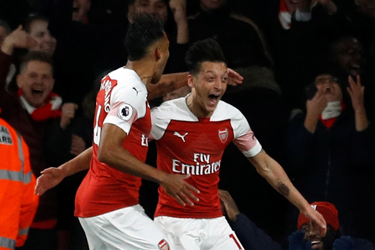 Arsenal's Pierre-Emerick Aubameyang celebrates scoring their third goal with Mesut Ozil during their 3-1 Premier League home win over Leicester City at the Emirates Stadium in London on October 22, 2018.