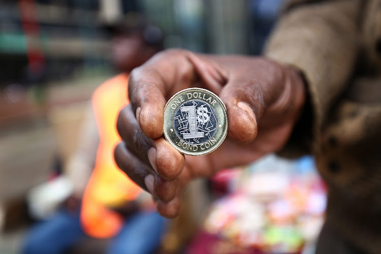 A man holds the one dollar bond coin in Harare, Zimbabwe. Picture: EPA/AARON UFUMELI
