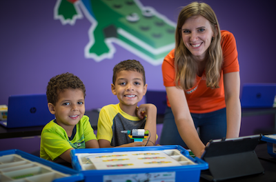 woman and two young boys smiling while learning LEGO Robotics