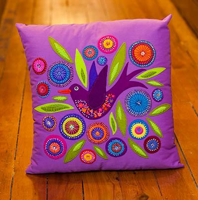 A colorful pillow on a wood surface  Description automatically generated with low confidence