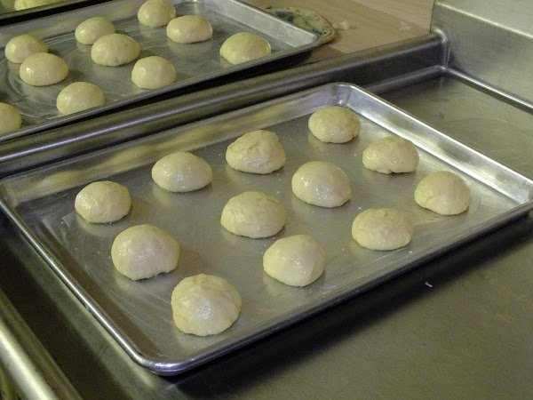 Form into balls and place on greased cookie sheets to raise (a dozen to...