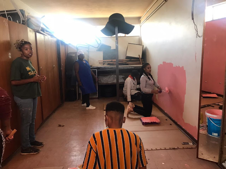 The Pink Forum team working on a classroom.