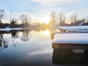 Photo: Sunset reflected in a lake with snow-covered stone bridge and wooden docks at Eastwood Park in Dayton, Ohio.