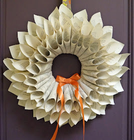 hanging wreath made of curled book pages adorned with orange ribbon