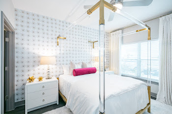 Model bedroom with wood-inspired flooring, white rug, and large white bed
