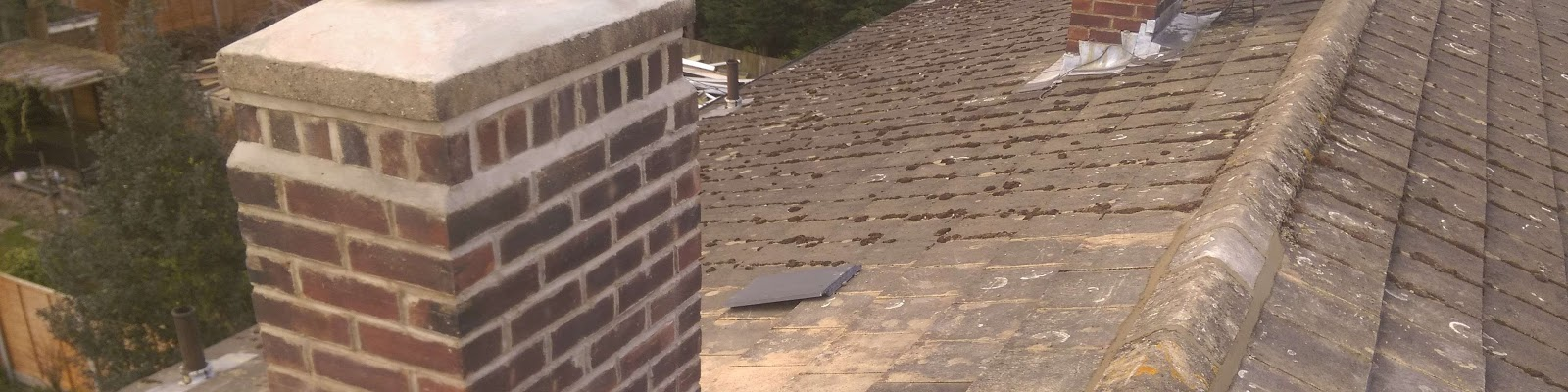An old roof with a chimney with recently installed slates