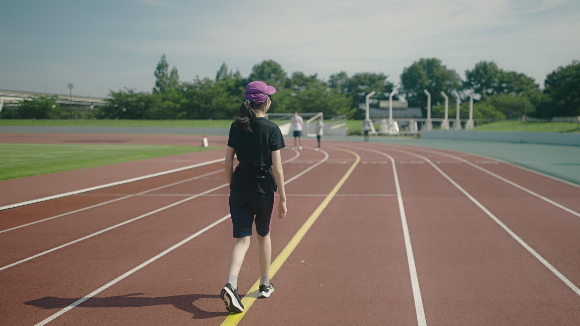 写真:アプリの挙動を確認しながらコース上を歩く高校生の女性のテスト走者。