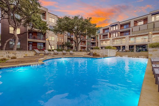 Apartment swimming pool with lounge furniture at dusk