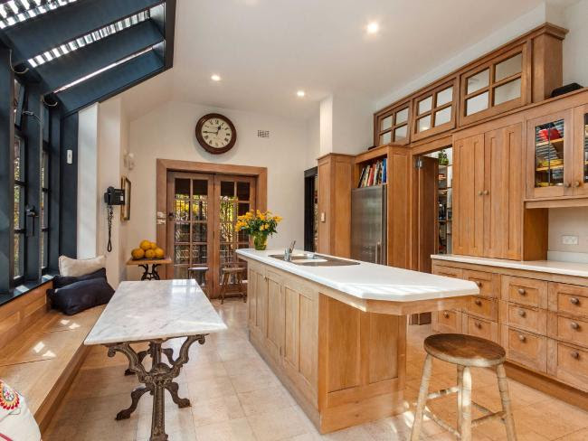 An updated kitchen has stone benches and an adjoining butler's kitchen.