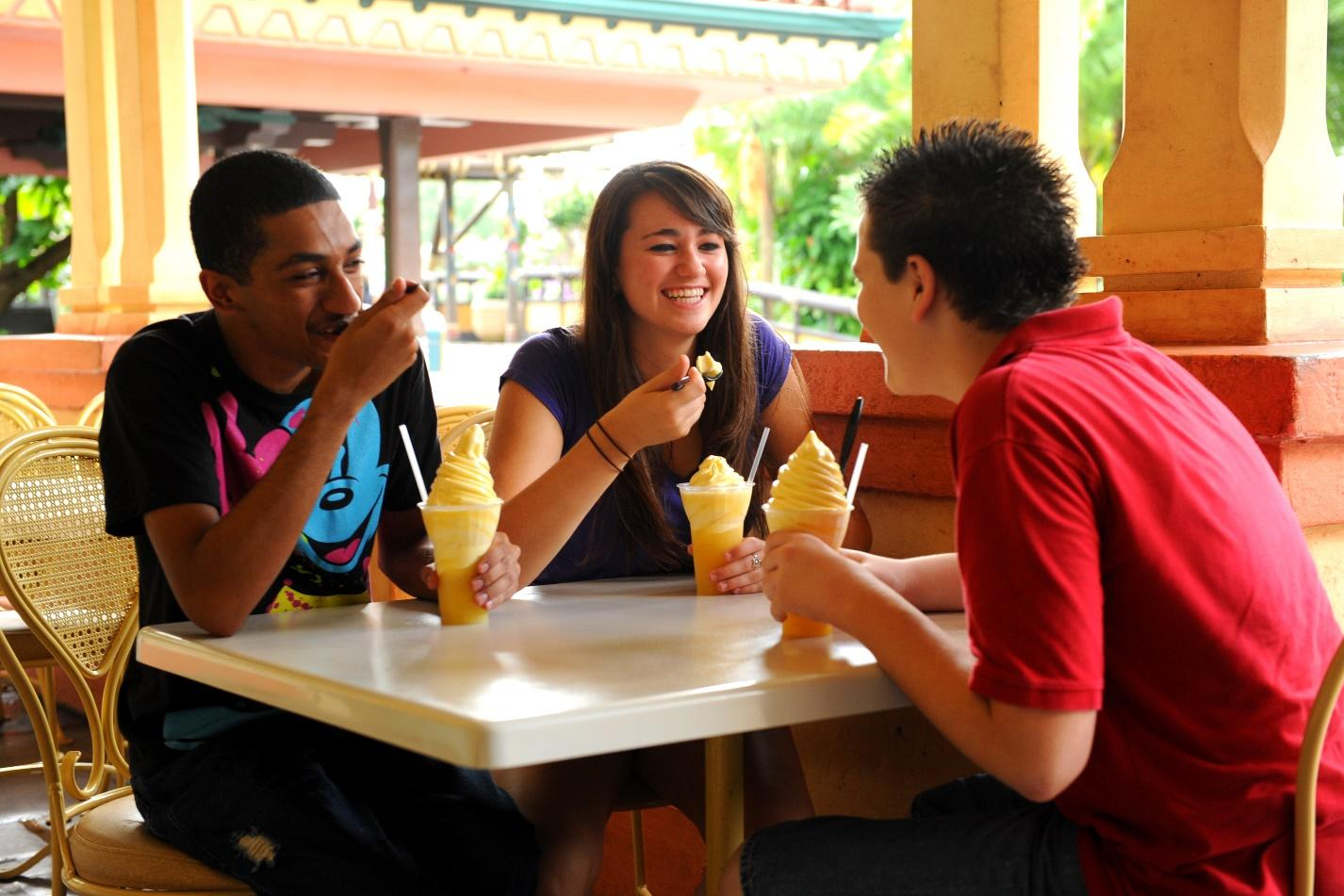 Two guys and a gal eat some ice cream together and laugh at Disney.