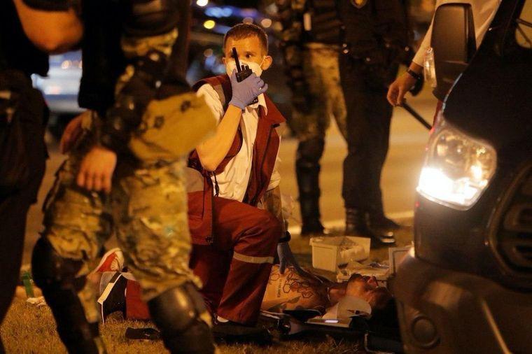 Врач скорой оказывает помощь пострадавшему участнику акций протеста в Минске