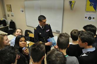 Photo: Le commandant, entouré des élèves, au moment de la distribution des cadeaux-souvenirs