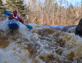 Photo: Kayaker Jonathan Sisley makes his way down one of the larger rapids on the Lester River as spectators look on.