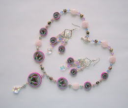 "Photo: PCB-105 Necklace and earrings set. Polymer Clay Butterfly cane beads, Swarovski Crystals, cloisonne and Rose quartz beads. The butterfly cane beads Diameter are 11/4"", 1"", and 5/8"". They are sanded and polished very smooth. At the bottom of the middle bead is a Swarovski Crystal Pendant 7/8"" x 5/8"". The necklace is 22"" long, and 3 3/4"" long for the middle pendent. The earrings are 3 1/2"" long. the Rose quartz beads diameters are 1/2"". $199.00. If you would like to buy this cane please go to Polymer Clay cane -> Butterfly - 3"