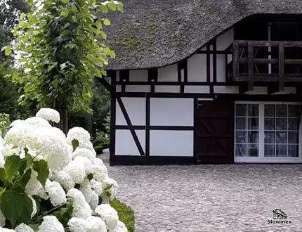 Elegancki dom z muru pruskiego i trzcinowym dachem z kamiennym brukiem w otoczeniu parkowym
