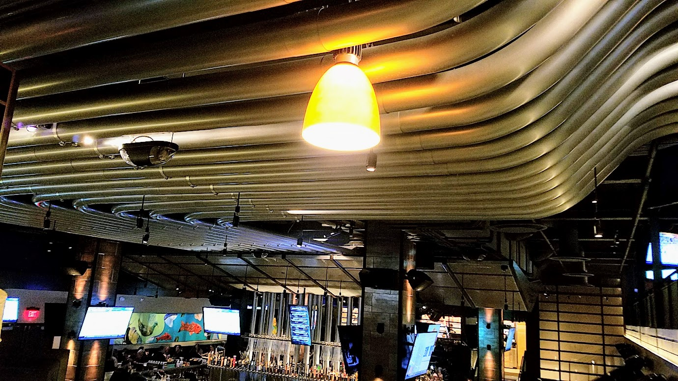 Yard House Portland offers 130 taps with a keg room holding over 5000 gallons of beer. When you are dining in the downstairs area, just look up: those metal cylinders carry six lines each, from the refrigerated keg room to the tap