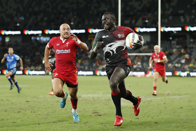 Kenya's Collins Injera races away from the Wales defence for a try during the Sydney Sevens