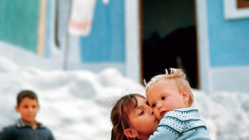 Una niña del barrio de las cuevas de la Alcazaba llevando en brazos y besando a su hermano pequeño.