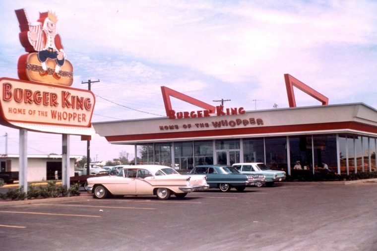 """The first Burger King location with a sign out front saying """"Burger King home of the Whopper""""."""