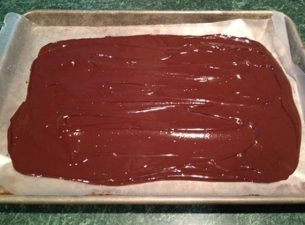 Spread melted chocolate evenly on baking sheet.