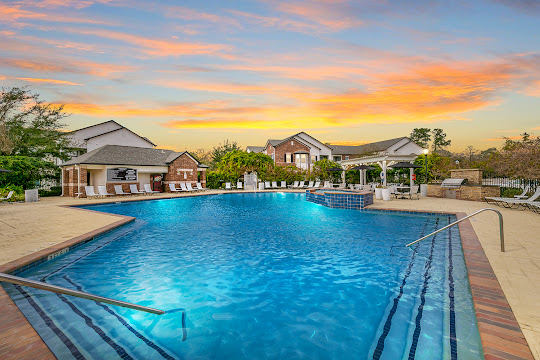 Villas at Cypresswood Apartments sparkling community pool at dusk