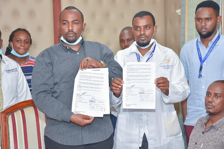 Garissa county secretary Abdi Ali and KMPDU Garissa chapter chair Dr Hassan Mohamed display the signed document after reaching an agreement