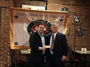 Photo: Chapter President Anthony Nigro presents a donation to Verona High School International Weekend faculty advisor David Fogel