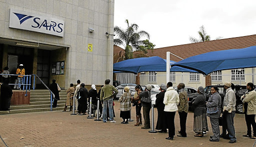 File photo of people queuing to submit their income tax returns to SARS.