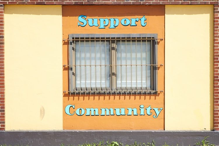 window in the wall of a building with the words Support and Community above and below it.