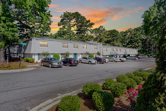 Nirvana at Riverdale apartment building with parking lot and entryway to units at dusk