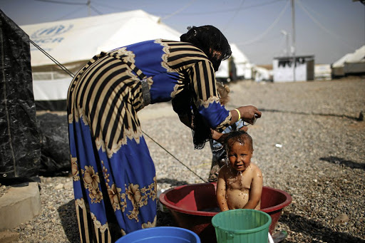 Tough times: A displaced boy is washed by a relative at Hammam al-Alil camp, south of Mosul, in war-ravaged Iraq on Wednesday. Picture: REUTERS