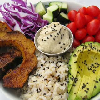 Brown Rice, Chili And Cinnamon Roasted Acorn Squash, Purple Cabbage, Cucumbers, Grape Tomatoes, Avocado, Hummus, And Sesame Seeds.