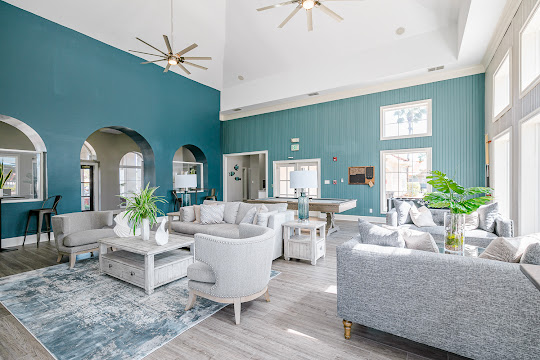 Clubhouse with wood-inspired flooring, blue accent walls, and plenty of seating