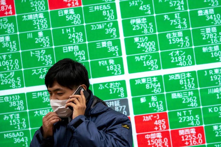 A man wearing a protective face mask talks on his cellphone in front of a screen showing the Nikkei index outside a brokerage in Tokyo, Japan. Picture: REUTERS/ATHIT PERAWONGMETHA