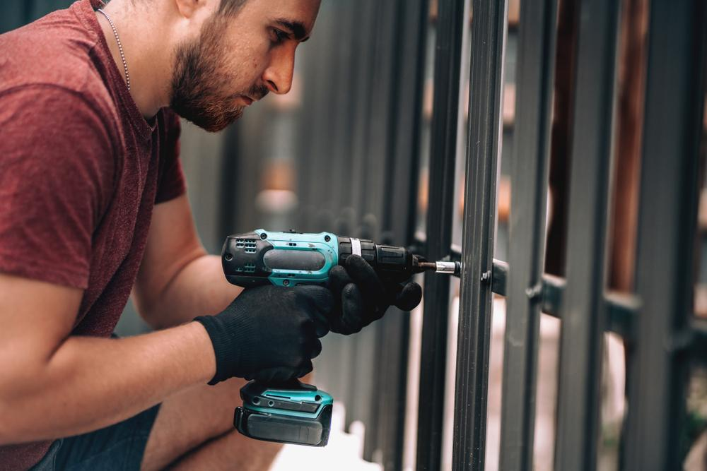 Close up of construction worker using screwdriver and drilling screws into metal fence