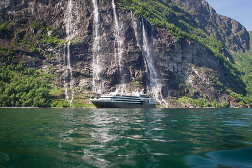 The Ponant ship L'Austral passes a waterfall in the Geiranger Fjord of Norway.