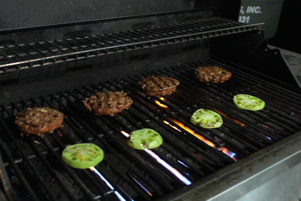 Four hamburgers and four tomatoes on a grill.