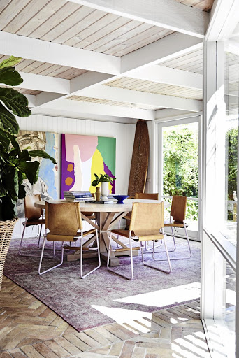 A wooden surfboard and colourful artworks add a hint of relaxed fun to the dining room.