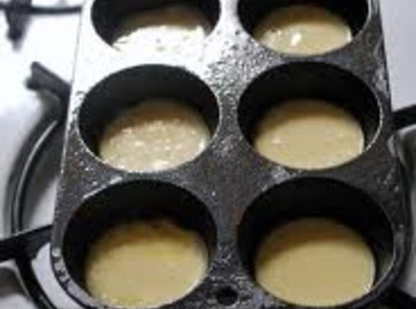 Brush the heated popover pans with the remaining 1 tablespoon of melted butter. Fill...