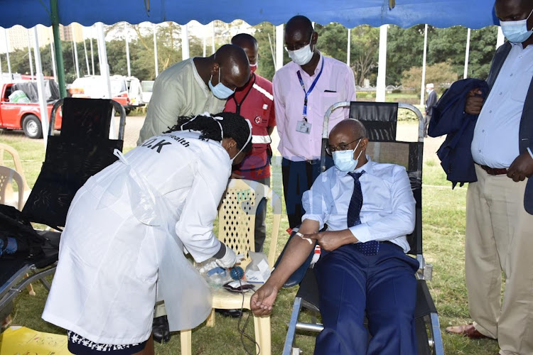 Health CAS Rashid Aman donates blood as a doctor from National Blood Transfusion Service Sophia Damaiyu holds the blood pint during the launch of blood donation drive at KICC Comesa grounds on June 12,2020.