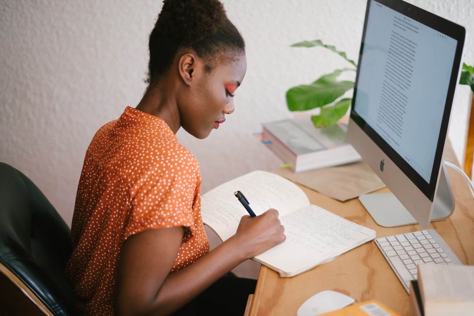 A woman in an orange shirt takes notes as she reads text on a Mac desktop computer.