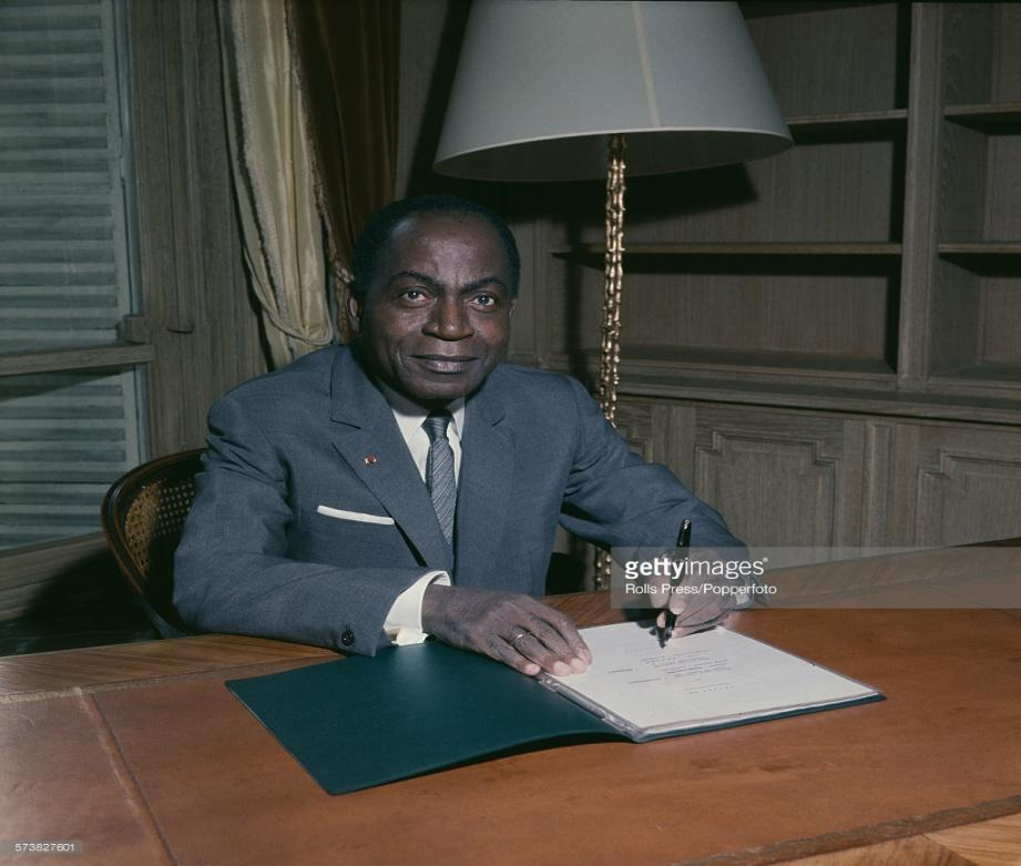 First President of Cote d'Ivoire, Felix Houphouet-Boigny (1905-1993) pictured sitting at an office desk signing papers in 1967.