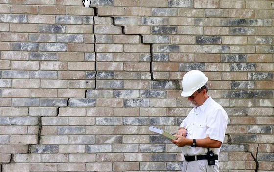 structural engineer analyzing foundation stair step crack