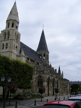 """Photo: The Notre Dame Collegiate Church (which derives its name from having been ministered to by a college of canons), originally from the 12th century on the remains of an older structure, is considered a beautiful example of the transition from Roman to Gothic architecture. There were extensive additions in the 14th, 15th, and 17th centuries; the Church suffered greatly during the Hundred Years War, the Wars of Religion and the Fronde. This damage led to major restoration work during the 19th century, the most famous by Viollet-le-Duc (from 1846 to 1861), who sought to restore the church's Roman character by eliminating the choir's Gothic bays and rebuilding a circular chapel in the chevet (""""a semicircular or polygonal east end of a church, especially a French Gothic church, often with a number of attached apses""""). The church houses the stone baptismal font of Saint Louis, a 1903 organ by Cavailles Coll-Mutin, and exceptional works of sacred art, particularly its woodworks and sculptures."""