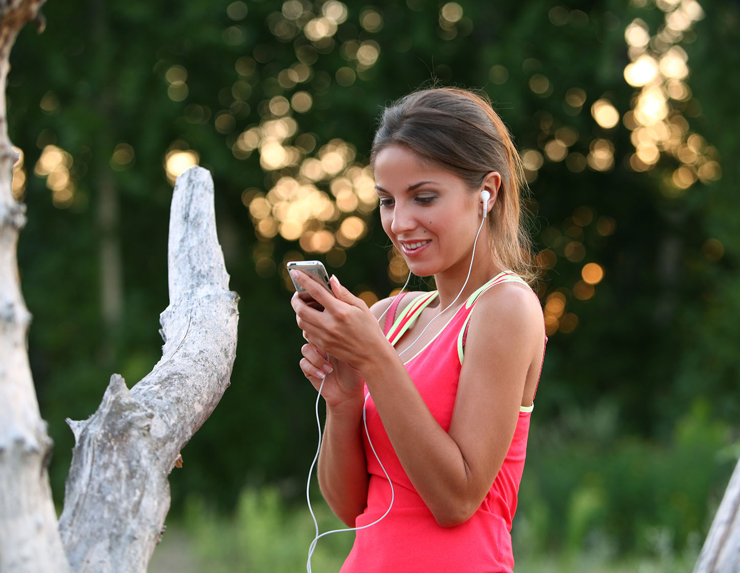 Young woman listening to a podcast while running