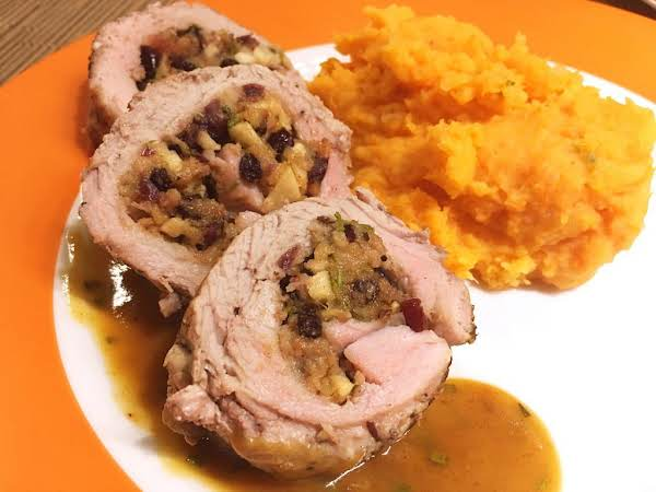 Three Slices Of Stuffed Pork, Drizzled With A Sauce Next To Mashed Potatoes.