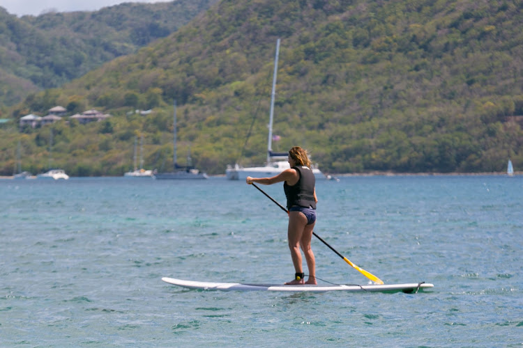 A Windstar passenger tries stand-up paddleboarding during the Windstar Island Experience beach party in St. Lucia.
