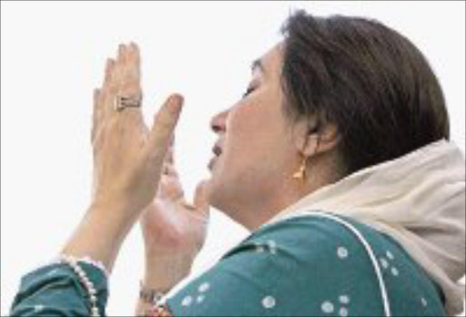 HOME: Benazir Bhutto prays as she arrives in Karachi. Pic. Petr Josek. 18/10/07. © Reuters.