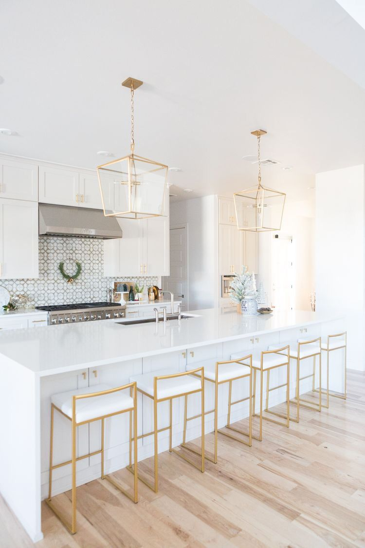a large white center island is surrounded by white and gold barstools. two gold pendant lights hang above. the cooking area is surrounded by white shaker cabinets